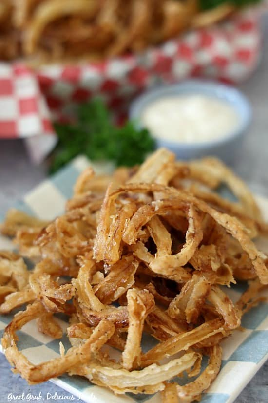 Friend Onion Strings on a blue and white checkered plate with small blue bowl filled with ranch, along with parsley in the background.