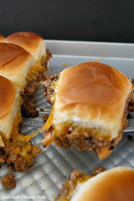 Cheesy Beef Sliders - a slider on a spatula with more sliders on the baking sheet below.