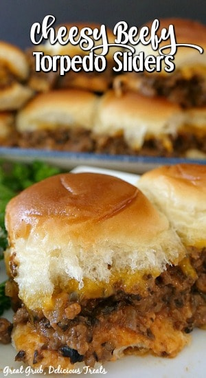 A stack of cheesy beef sliders with 2 in front, that are loaded with a ground beef mixture and cheese in between Hawaiian rolls.