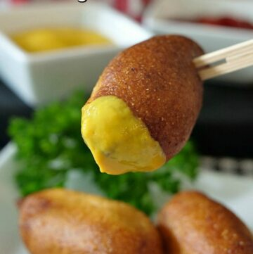 three mini corn dogs with one dipped in mustard and a small white bowl in the background with mustard.
