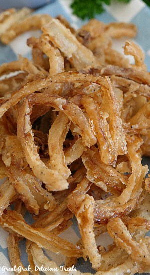 Close up picture of Fried Onion Strings on a white and blue checkered plate.