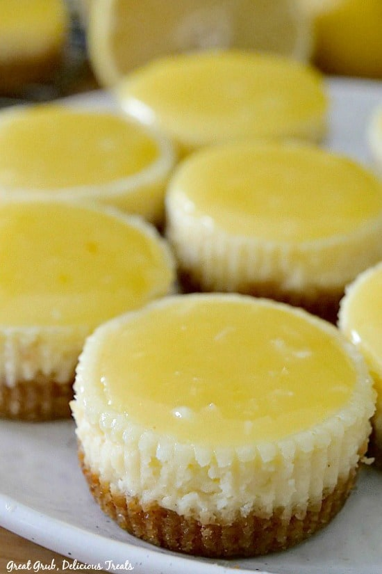 Mini lemon cheesecakes with lemon glaze on a white plate with a lemon half in the background.