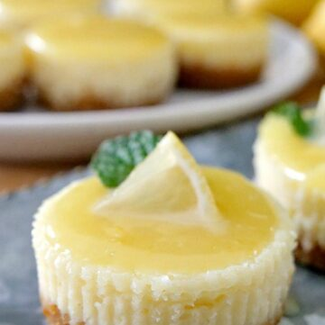 A mini lemon cheesecake with a small lemon wedge and piece of mint on top with mini cheesecakes on a white plate in the background.