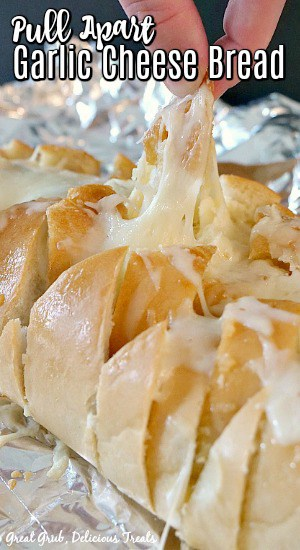 Pull Apart Garlic Cheese Bread - a photo of the French loaf stuffed full of melted cheese and a piece being pulled apart from the loaf.