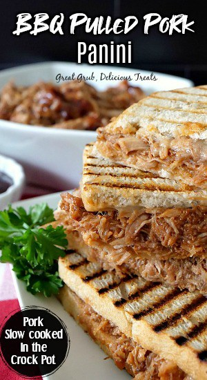 BBQ panini sandwich on a white plate with a white bowl of pulled pork in the background.