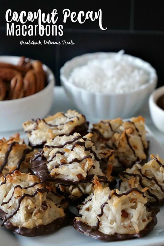 Coconut pecan macaroons piled up on a white plate with small white bowls of coconut flakes, pecans, and chocolate in the background.