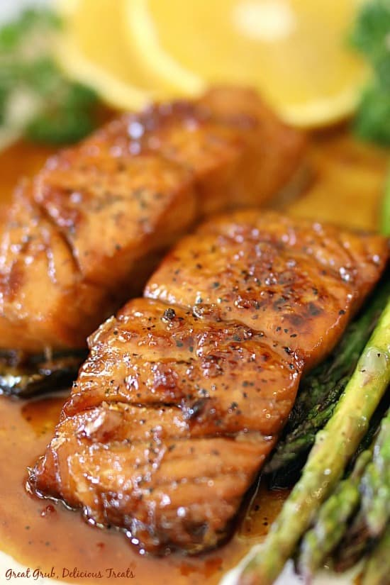 Honey glazed salmon on a white plate with asparagus to the right side of plate and orange slices and greenery in the background.