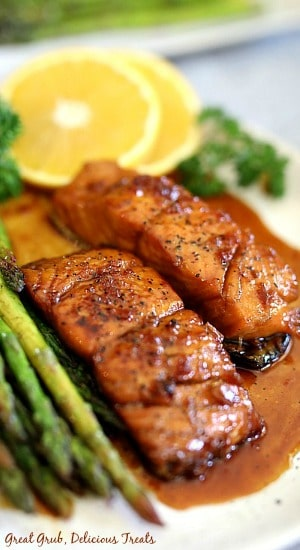 Honey glazed salmon on a white plate with asparagus on plate and lemon slices in the background.