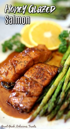 Honey glazed salmon on a white plate with asparagus and lemon slices in the background.
