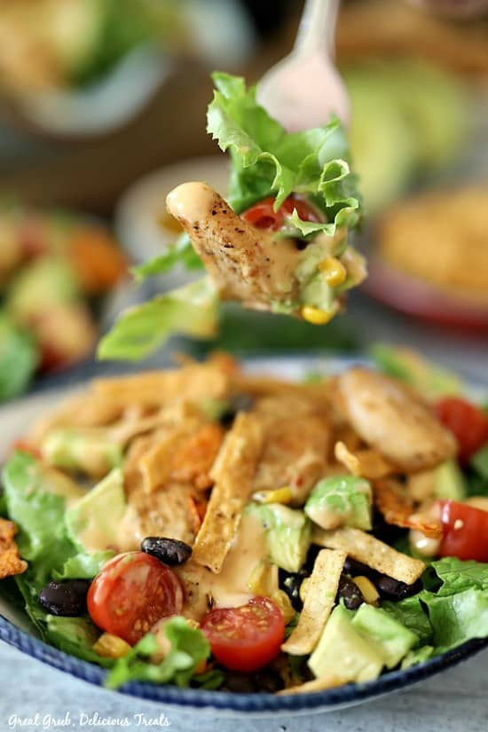 A bite of southwest grilled chicken salad on a fork with chicken, corn, tomatoes, and lettuce with a large white bowl full of salad in the background.