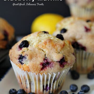 A photo of a blueberry muffin on a white plate with blue trim and a lemon and another muffin in the background.