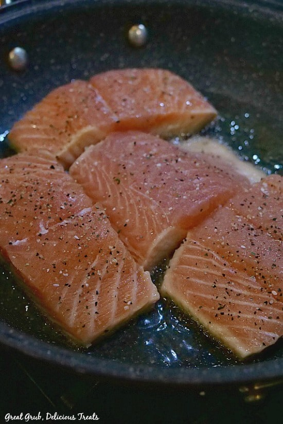 Four salmon fillets searing in oil in a skillet pan, skin side down.