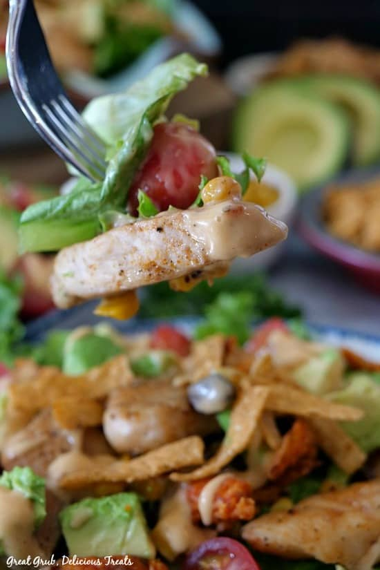A close up photo of a bite of southwest grilled chicken salad with lettuce, tomato, chicken, corn, and dressing atop of a large bowl of salad.