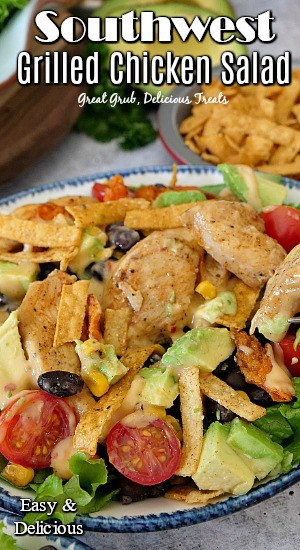 Southwest grilled chicken salad in a white bowl with a blue trim. Salad is topped with chicken, corn, black beans, avocados, and tomatoes.