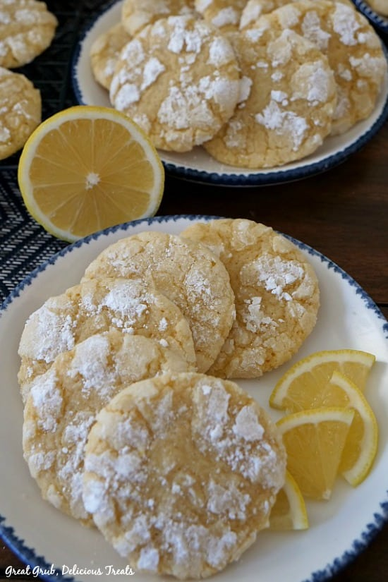 5 lemon crinkle cookies with lemon wedges on a white plate with blue trim and another white plate with blue trim in the background with lemon crinkle cookies layed out on it.