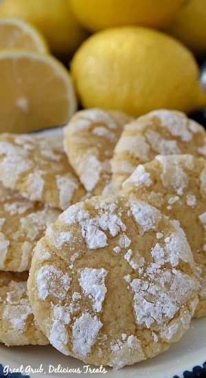 A close up photo of lemon crinkle cookies on a white plate with lemons in the background.