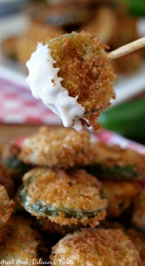 A close up photo of fried jalapenos with one on a stick and dipped in ranch dressing.