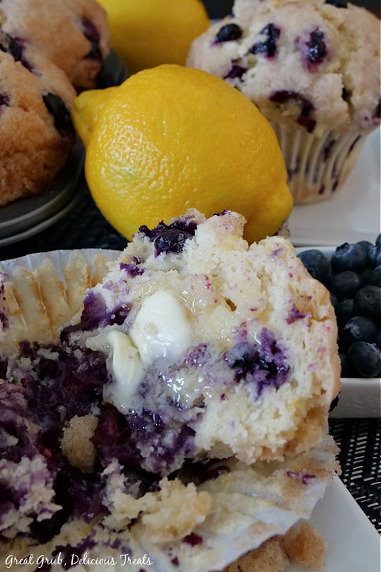 A close up picture of a Texas-Sized Blueberry Muffin cut in half with a chunk of melted butter on the inside. Muffins in the muffin pan and a muffin on a white plate are in the background, along with a lemon and a small bowl full of blueberries.