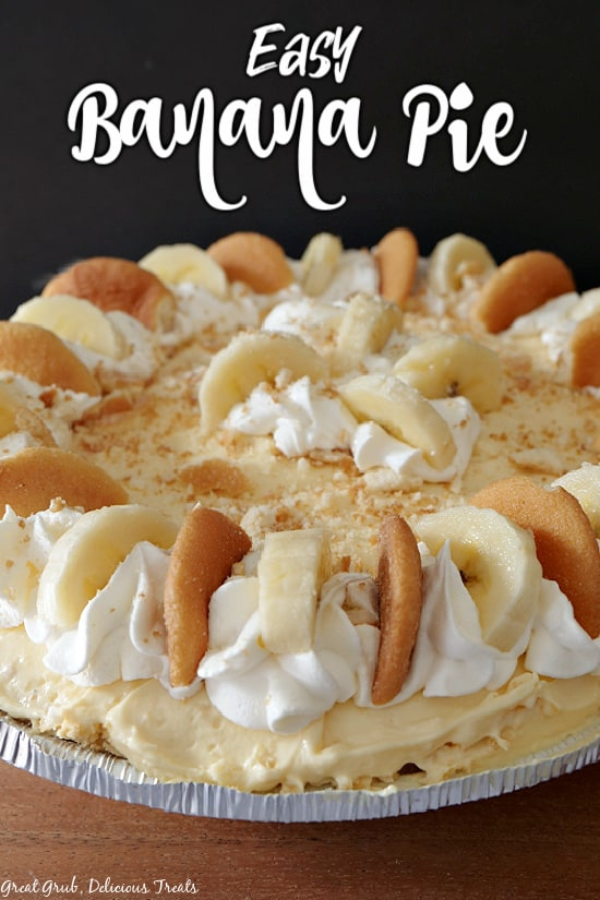 Easy Banana Pie - a no bake banana pie shown in a pre-made graham cracker crust, with sliced bananas, vanilla wafers and cool whip on top of the whole pie.