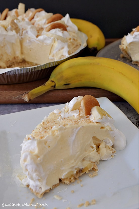 A slice of easy banana pie on a white plate with the pie, two bananas and another slice of pie in the background.