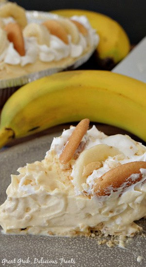 A photo of a piece of easy banana pie, topped with sliced bananas, cool whip and vanilla wafers on a grey plate with a couple bananas and the whole pie in the background.