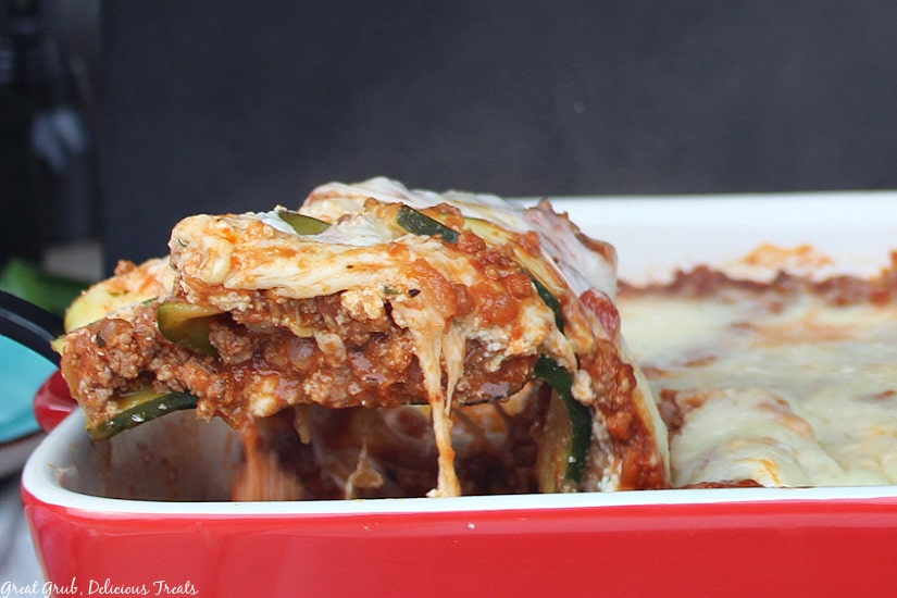 Red baking dish with a spatula full of zucchini lasagna being dished out of the baking dish.