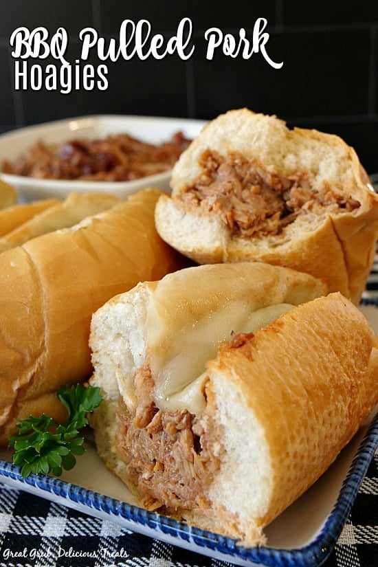 BBQ Pulled Pork Hoagies on a white plate with blue trim, with a white bowl full of BBQ pulled pork in the background.