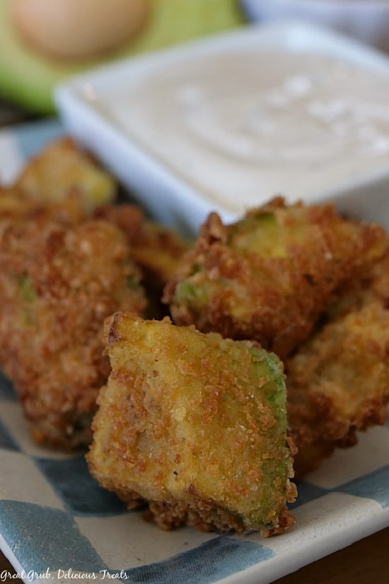 A small pile of crispy fried avocado bites on a light blue and white checkered plate with a small white square bowl filled with ranch dressing for dipping on the plate as well.