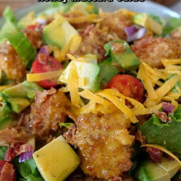 Close up photo of a crispy chicken salad with fried chicken bites, avocado, tomatoes, cheddar cheese, and chunks of bacon.