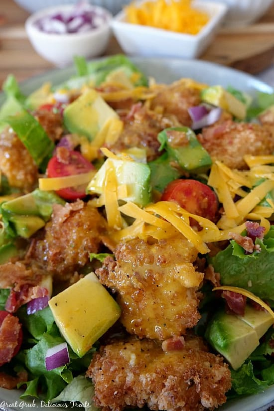A close up photo of crispy chicken salad topped with chicken, avocados, tomatoes, cheddar cheese, and diced red onion.