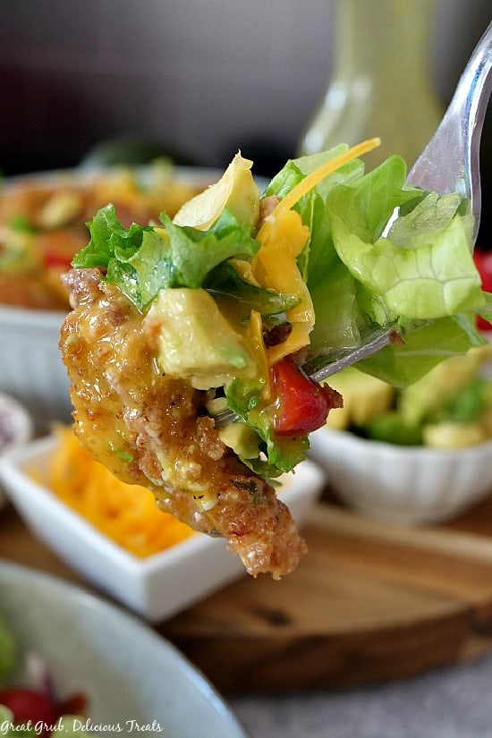 A close up photo of crispy chicken salad on a fork with lettuce, a piece of chicken, avocado, tomato, and cheddar cheese.