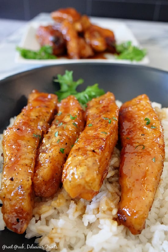 A close up photo of Lemon Honey Glazed Chicken strips on a bed of white rice in a black bowl.
