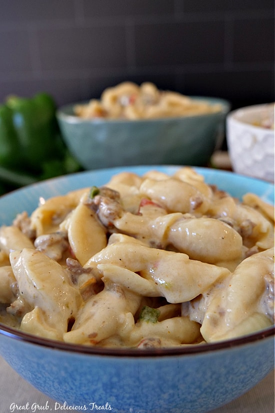 A blue bowl filled with creamy Italian sausage pasta with two other bowls in the background.