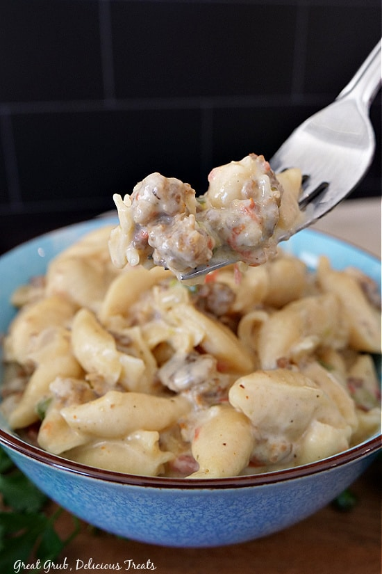 A forkful of creamy Italian sausage pasta being held over a blue bowl filled with the pasta recipe.