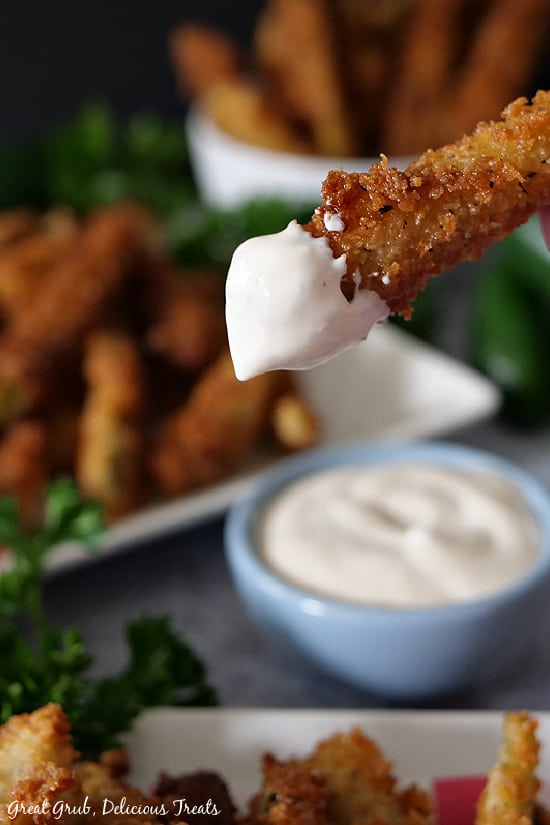 A photo of a crispy jalapeno fry being held up after being dipped in ranch dressing with more jalapeno fries in the background on a plate and in a white bowl.
