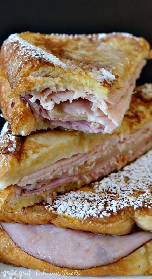Monte Cristo sandwiches cut in half, stacked on top of each other with powdered sugar on top.