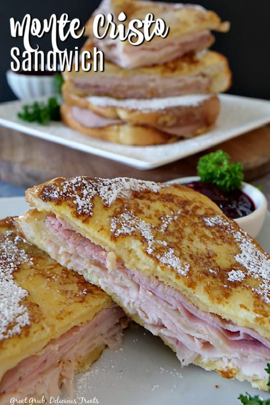 Monte Cristo Sandwich cut in half on a white plate with a small bowl of raspberry jam and more sandwiches in the background.