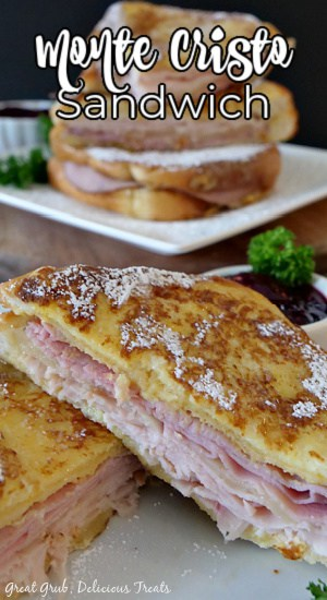 A monte cristo sandwich, cut in half, sitting on a white plate with a small white bowl of raspberry jam in the background, along with another sandwich stacked up on a white plate in the background.