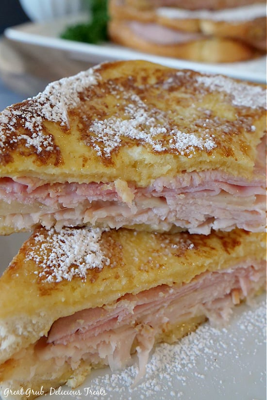 A Monte Cristo Sandwich cut in half on a white plate showing the ham, Swiss and turkey meat between Texas toast that has been pan fried, then dusted with powdered sugar.