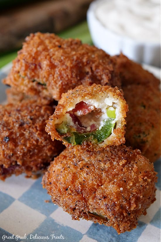 A close up view of a stack of stuffed jalapeno poppers with a bite taken out of one showing the jalapeno, cream cheese mixture and bacon all sitting on a blue and white checker plate.