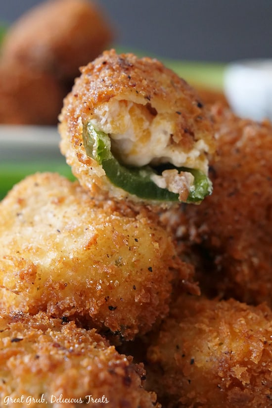 Another close up view of a stuffed jalapeno popper that has a bite taken out sitting on a stack or more poppers.
