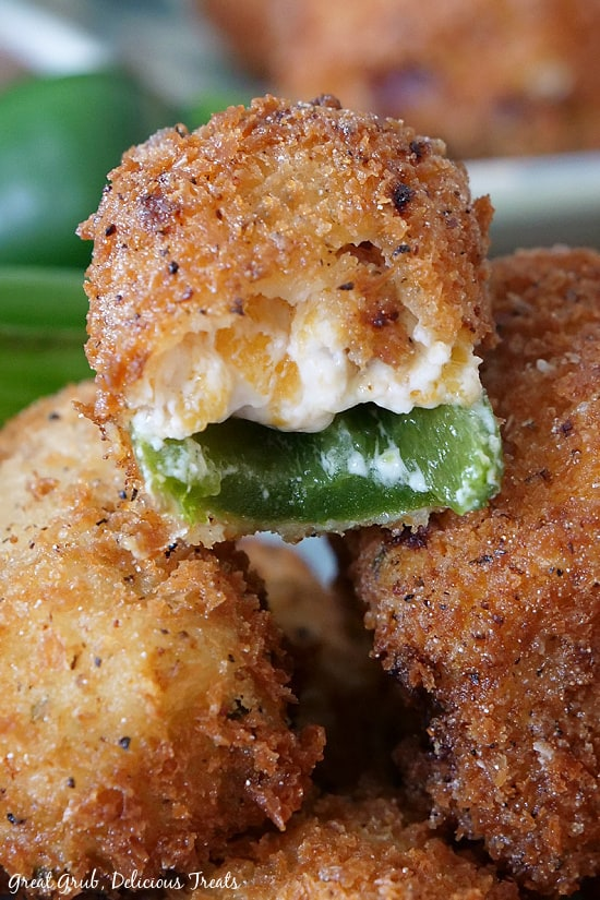 An extreme close up of a Stuffed Jalapeno Popper with a bite taken, sitting on top of two others, showing the jalapeno and cream cheese mixture.