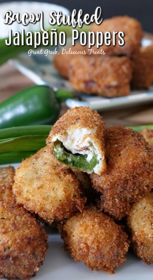 Stuffed jalapeno poppers stacked up on a white plate with a bite taken out of one of them, with green onions and a jalapeno in the background, and another white plate with jalapeno poppers stacked up.