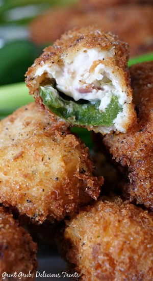 Stuffed jalapeno poppers stacked up and a bite taken out of a popper where you can see the jalapeno and the cheesy filling.