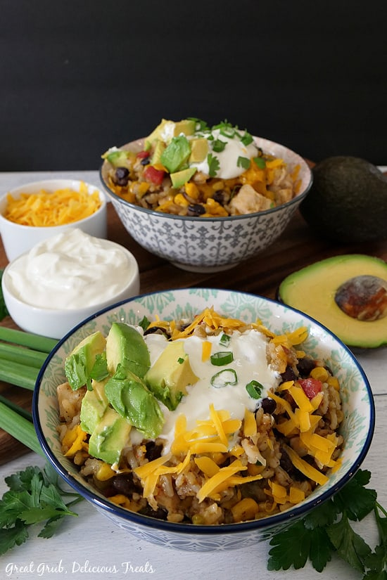 Two bowls filled with deliciously seasoned chicken, rice, beans, corn, topped with cheese, avocados, sour cream, green onions and cilantro, with sour cream and corn in little white bowls, with a half avocado and a whole avocado in the background.
