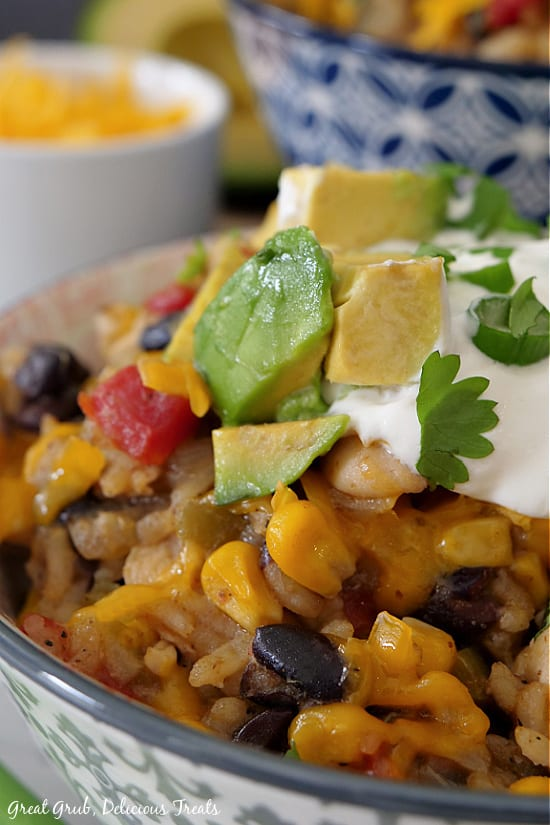 A close up bowl of southwest chicken bowl showing chicken, rice, corn, beans and topped with avocados, sour cream and cilantro.
