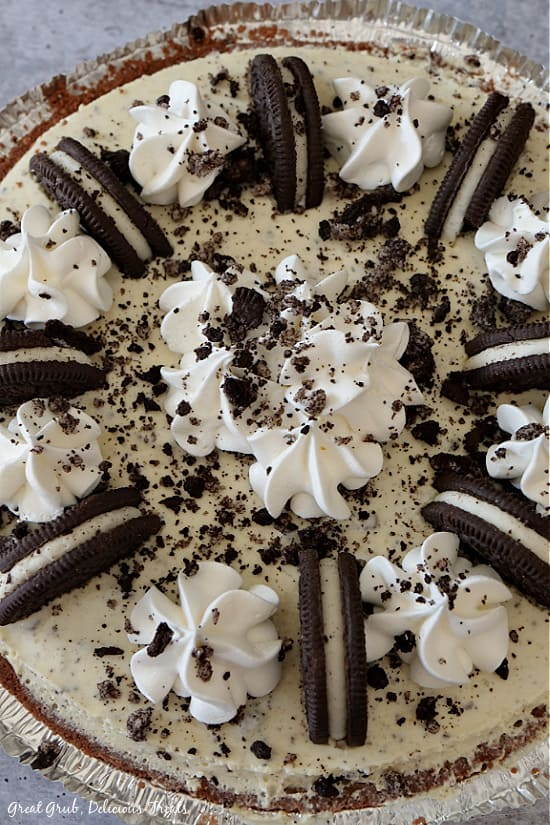 A whole No Bake Oreo Pie in a pre-made chocolate crust showing cookies, whipped cream and cookie crumbs on top.