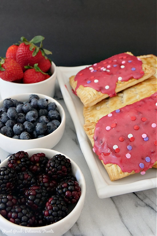 Homemade Pop Tarts with strawberry glaze with candied sprinkles on top placed on a white plate with a small bowl of strawberries, blueberries and blackberries along the side of the white plate.