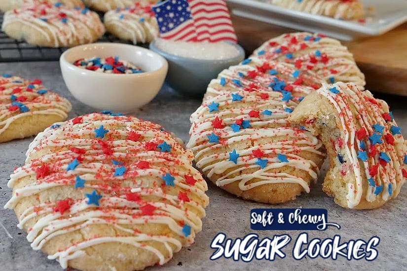 Patriotic Sugar Cookies drizzled with white chocolate with red, white, and blue sprinkles and stars on a grey surface with a white bowl with stars in it and an American flag sitting on a bowl of sugar.