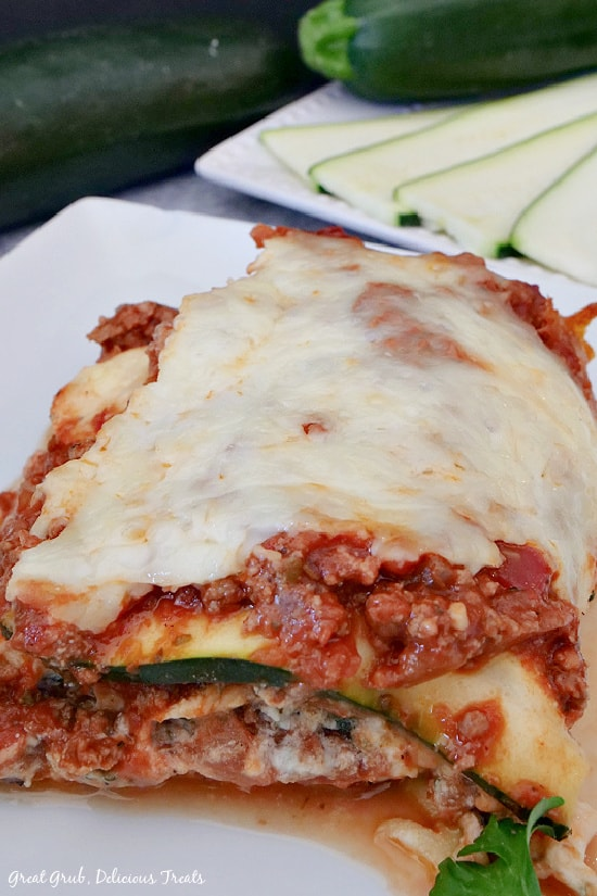 A serving of zucchini lasagna on a white plate with sliced zucchini in the background.